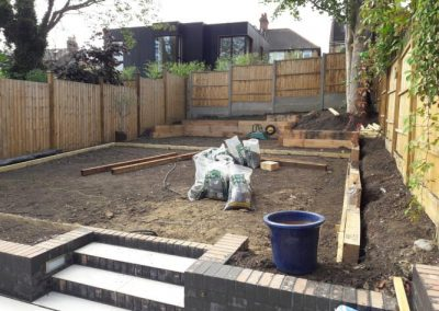 garden materials on soil in back garden with wooden fence