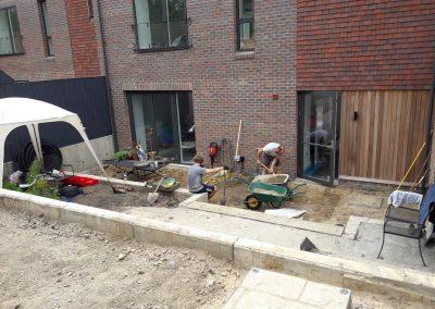 men working on landscaping back garden