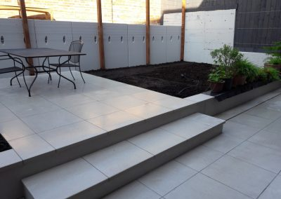 white patio with steps with table and chairs