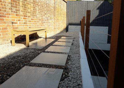 flagstones on pebbled ground with brown bench and fence