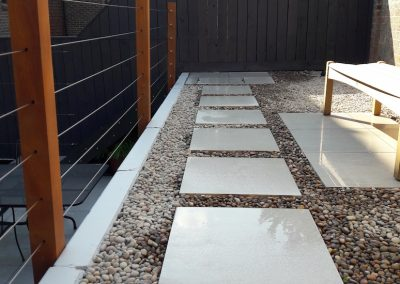 large flagstones in pebbled ground with bench