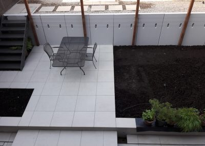 white patio with metal table and chairs with flower beds