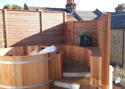 wooden hottub with steps surrounded by wooden fence