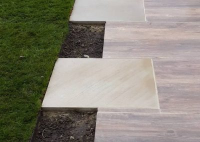 flagstones next to lawn with planting areas