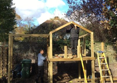 Two men building outdoor playhouse