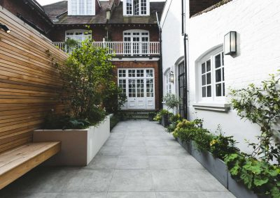 Contemporary courtyard with grey patio and planter boxes
