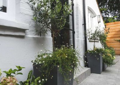 black planters along back of house wall