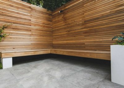 Cedar bench on white supports with wooden batten fencing