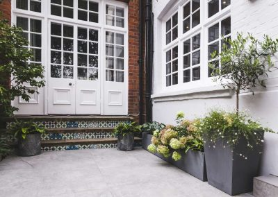Large white patio door with Moroccan style encaustic tiles in contemporary courtyard