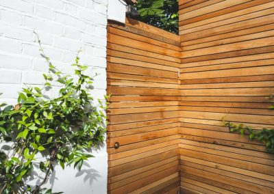 wooden batten fencing with concealed closed door in contemporary garden