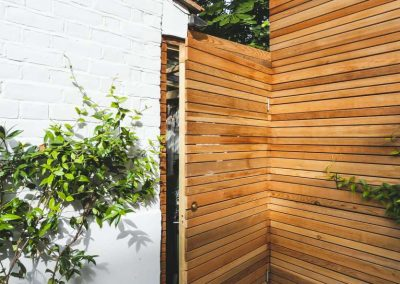 wooden batten fencing with concealed door in contemporary garden