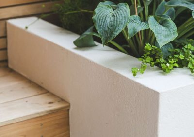 plants in white planter box on wooden steps