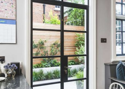 large glass office door looking out onto batten fencing and raised flowerbeds
