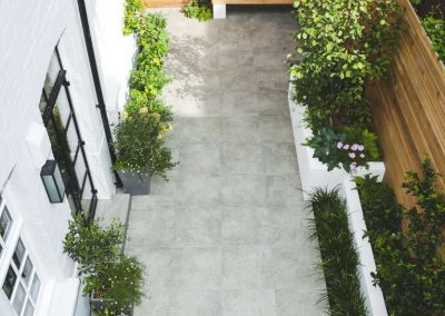 ariel view of long patio with grey flagstones and white planters