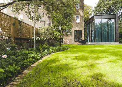 curved flowerbed around lawn leading to glass office