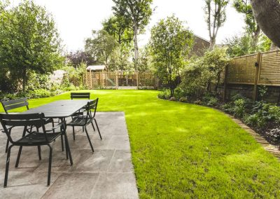 patio table and chairs on grey flag stones in large garden with play area at the end of the garden