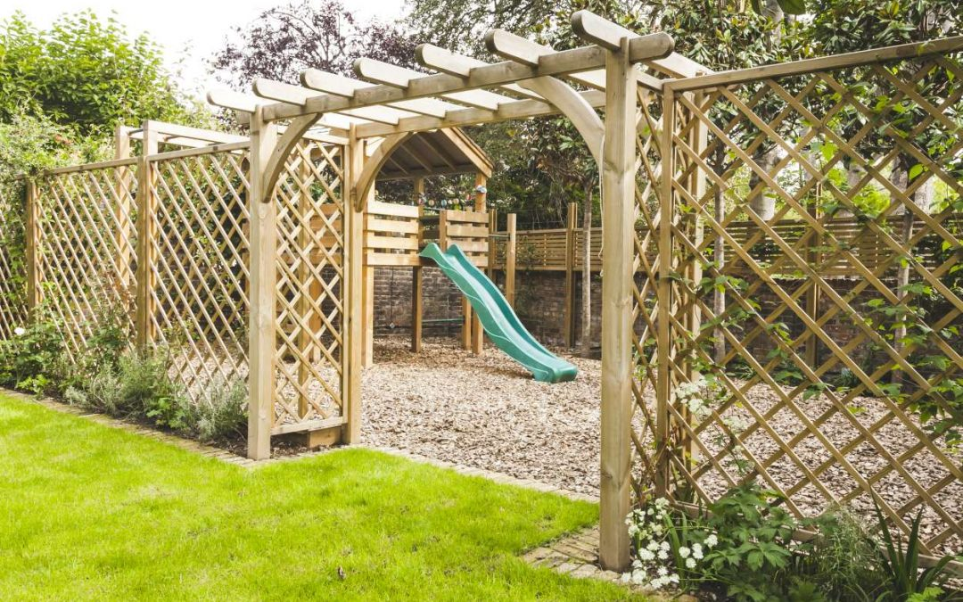 latticed fence leading to children's wooden play platform with swing