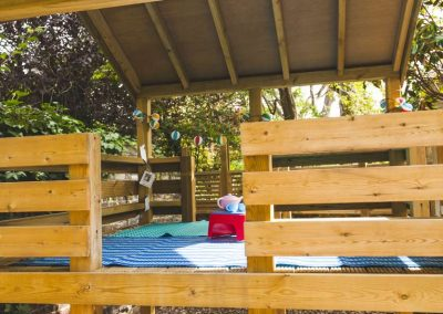 children's wooden play platform with green monkey bars