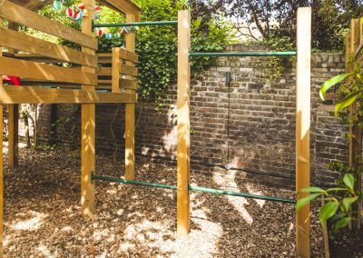 green metal bar forming climbing frame on wooden children's play platform