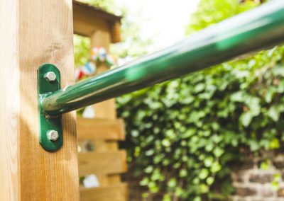 green metal bar in a wooden fencepost on children's play platform