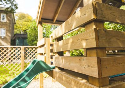 wooden children's play platform with green slide