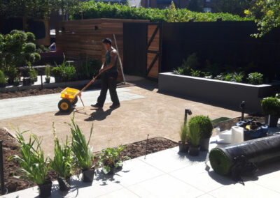 man flattening pave stones in newly constructed garden