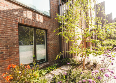 small flower bed with a tree in front of terraced house
