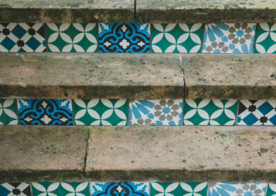 blue and green encaustic tiles decorating grey steps
