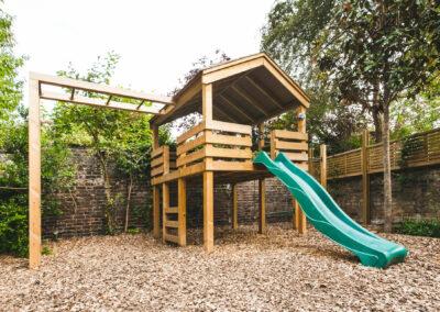 Children's wooden climbing frame with green slide in back garden