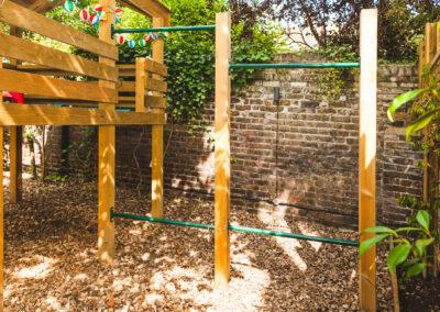 children's climbing frame and wooden platform in private garden