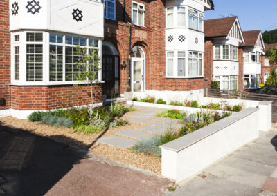 small plants, gravel and grey slabs in low maintenance front garden