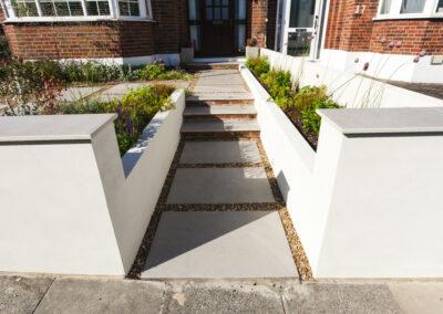 grey steps leading to front door in low maintenance front garden