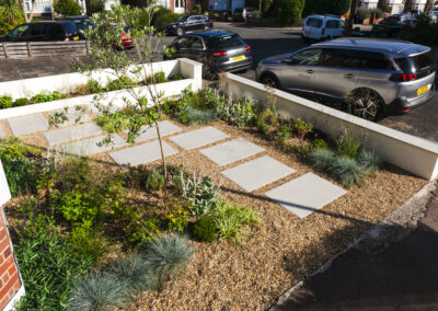 small plants and grey steps on gravel in low maintenance front garden