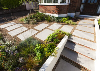 grey slabs on gravel with flowers in low maintenance garden