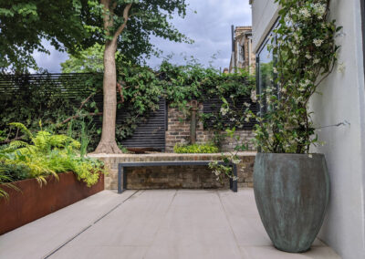 large grey vase with tall plant on grey patio with bench and brick wall
