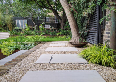grey pavement slabs on gravel at the back of a contemporary garden