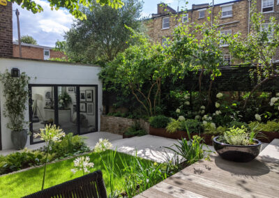 contemporary garden with raised decking, large seating area and white plants