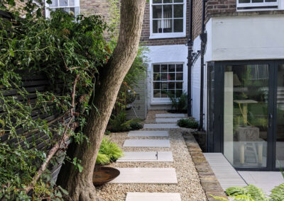 square pavement slabs on gravel leading to side of a house