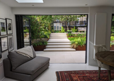 view from sitting room out to the garden with wide steps and raised decking
