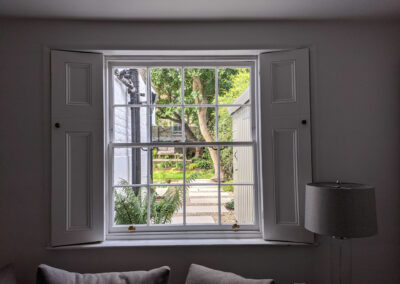view from large sash window with shutters out to the garden