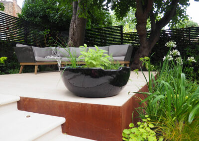 large black vase with plants on raised wooden decking in contemporary garden
