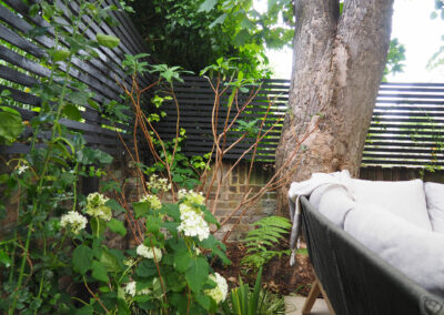 plants and black fencing behind large couch in a contemporary garden