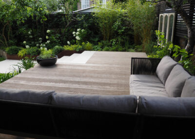 large couch on wooden decking in large contemporary garden
