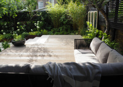 large seating area on wooden decking in contemporary garden