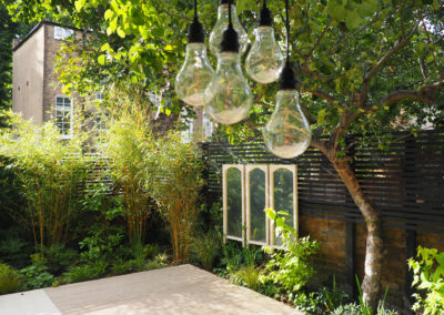 light bulbs hanging from tree in large contemporary garden