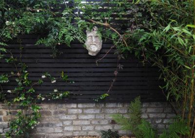 gargoyle on black fence surrounded by climbing plants