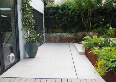 patio with porcelain tiles with large vase in contemporary garden