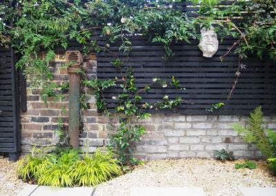 gargoyle on black fencee surrounded by foliage in contemporary garden