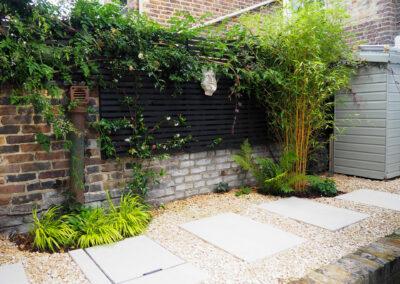 gargoyle on black fence in contemporary garden
