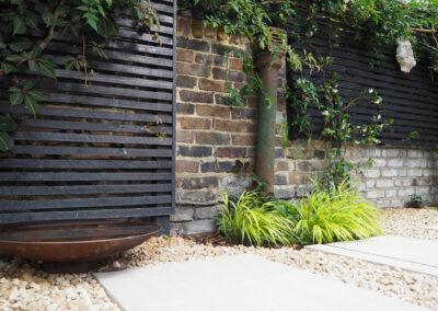 Water feature, gargoyle and black fencing in contemporary garden